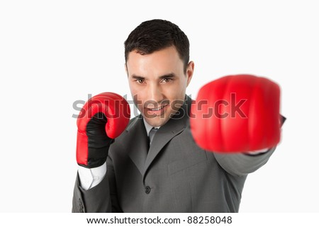 Businessman with boxing gloves on beating against a white background