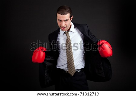 Businessman with boxing gloves on dark background