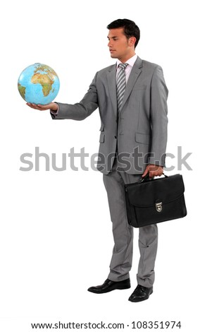 Businessman with briefcase holding globe