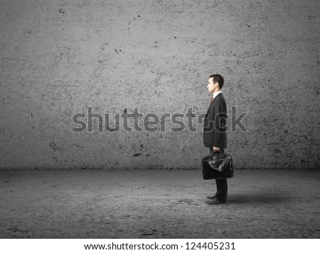 businessman with briefcase in concrete room