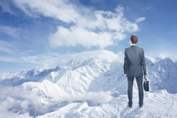 businessman with briefcase looking to winter mountains