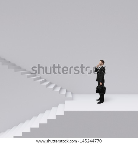 businessman with briefcase standing near ladder