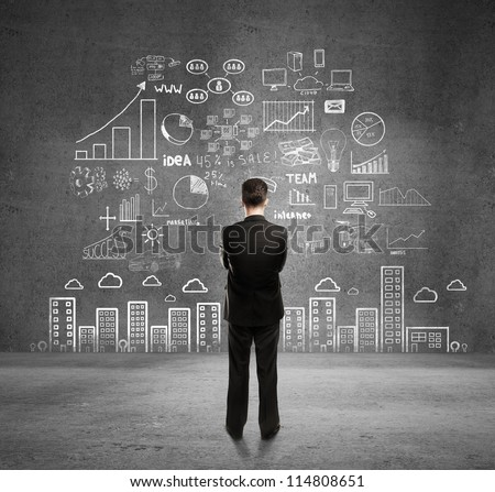Businessman With Business Plan Concept On Wall