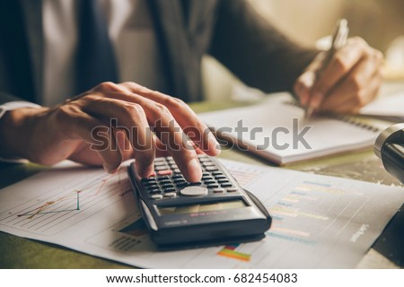 Businessman with calculator counting making notes at office hand is writes in a notebook