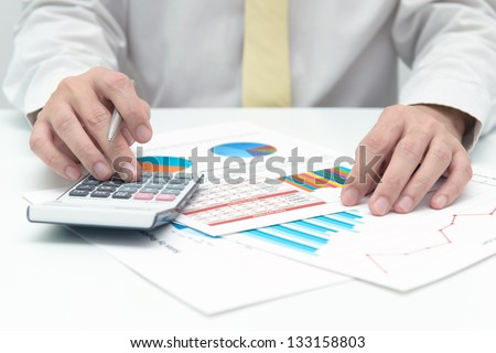 Businessman with calculator doing business data analysis
