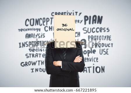 Businessman with cardboard box on head. Light backgroud with inspirational text. Be original concept #667221895