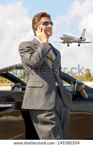 Businessman with cellphone near the car
