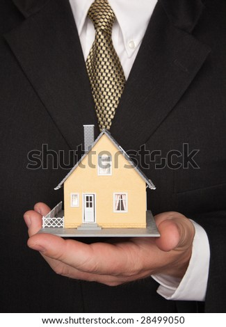 Businessman with Coat and Tie Holding House.