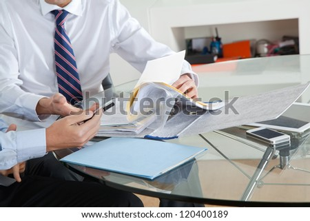 Businessman with colleague discussing paperwork at desk in office