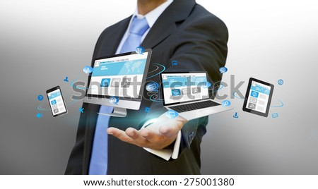 Businessman with computer phone and tablet in his hand