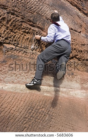 Businessman with cravat climbing a rock