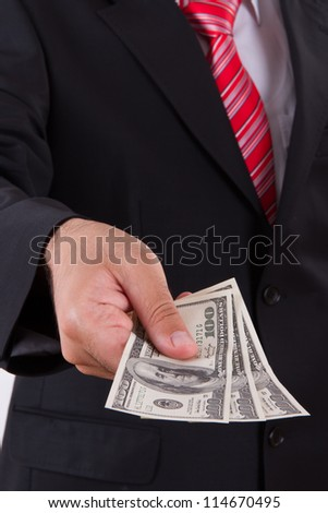 Businessman with dark jacket and red tie giving bills, one hundred dollars money.