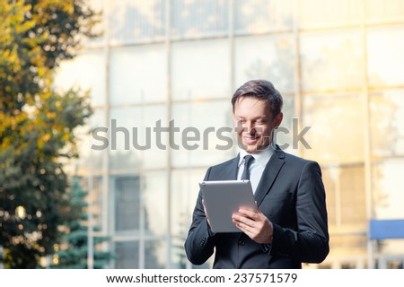 Businessman with digital tablet outdoors. Confident young man in formal wear working on digital tablet and smiling while standing against office building.