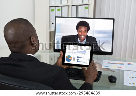 Businessman With Digital Tablet Video Chatting With Male Colleague On Computer In Office