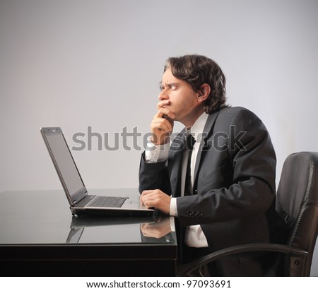 Businessman with doubtful expression in front of a laptop