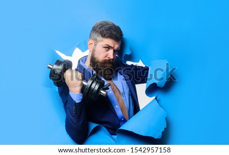 Businessman with dumbbell looking through paper hole. Power. Strength. Sport. Sporty bearded man with dumbbell. Fitness with equipment. Workout. Healthy lifestyle. Discount. Season sales. Copy space.