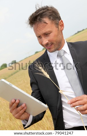 Businessman with electronic tablet standing in wheat field