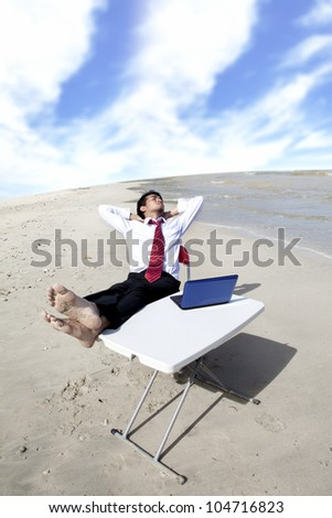 Businessman with feet over the table relaxing at the beach