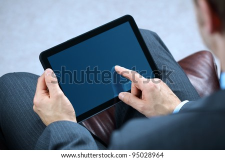 Businessman with finger touching screen of a digital tablet whilst sitting on a sofa #95028964