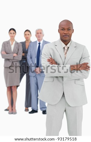 Businessman with folded arms and team behind him against a white background