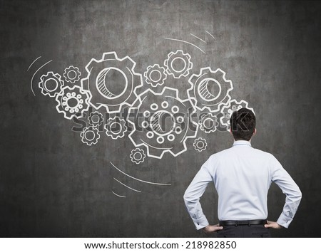 Businessman with gears - A concept of well organized work process.