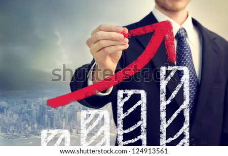 Businessman with graph representing growth above the city