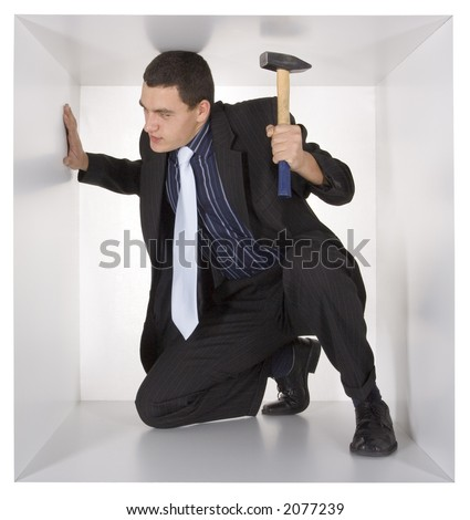 businessman with hammer in the cramped white cube