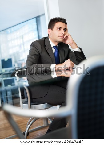businessman with hands on temple in meeting room