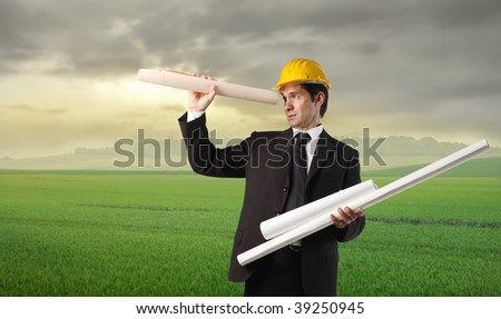 businessman with hardhat and blueprint rolls in a grass field
