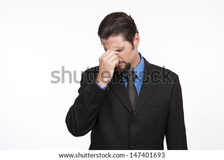 Businessman with headache pinching top of his nose