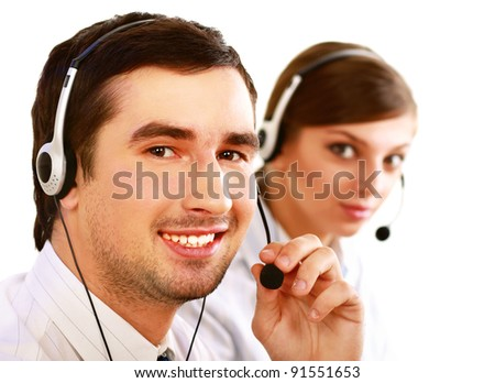 Businessman with headset smiling at camera in call center. Businesswoman in headset on background