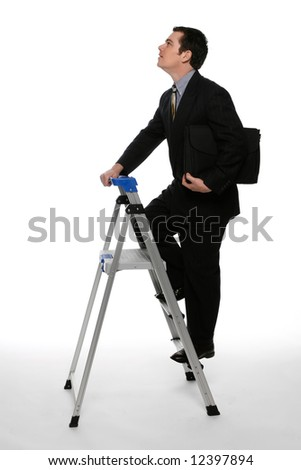 Businessman with his briefcase clutched under one arm climbing  up a stepladder with his gaze focused on the ceiling. Isolated against a white background - stock photo
