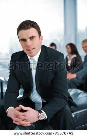 Businessman with his co-workers in office smiling, looking at camera