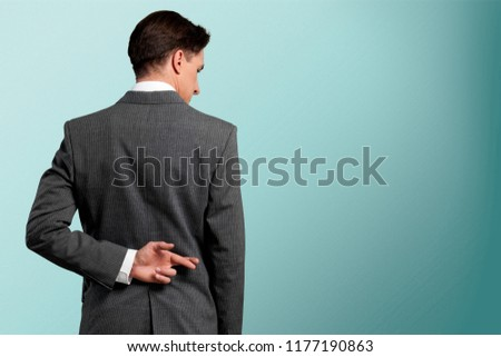 Businessman with his fingers crossed behind his back - concept for good luck or dishones #1177190863