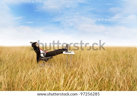 Businessman with his freedom of work anywhere. Relaxing outdoor with laptop computer. - stock photo