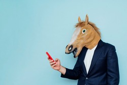 Businessman with horse mask using smartphone