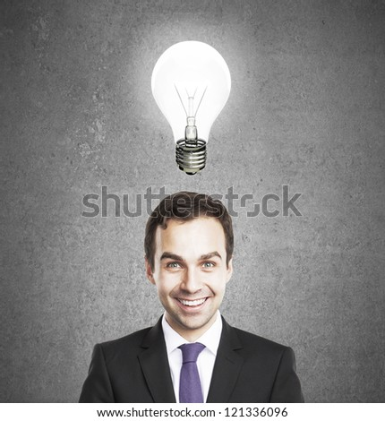 businessman with lamp concrete background