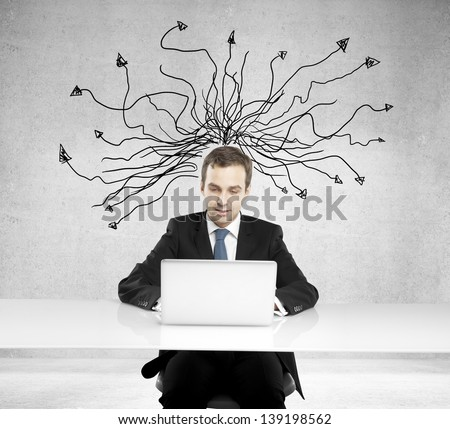 Businessman with laptop and arrows over head
