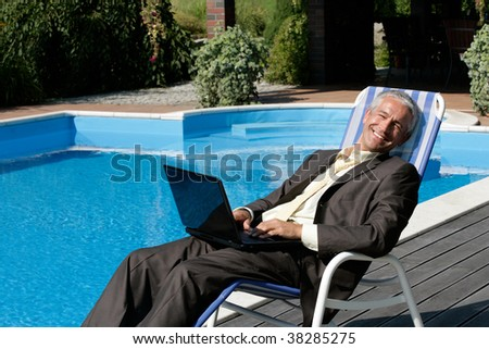Businessman with laptop computer resting on deck chair next to swimming pool