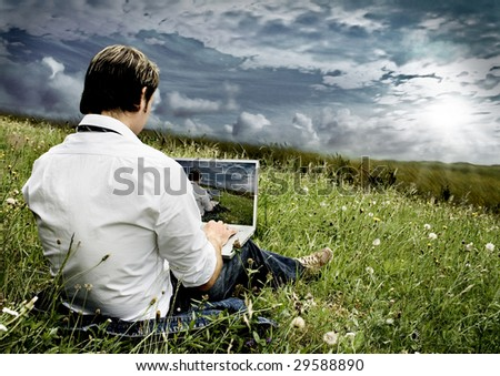 businessman with laptop on a field with dark clouds