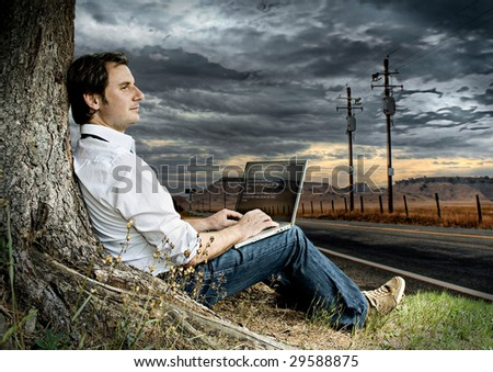 businessman with laptop on a meadow beside a road with dark clouds behind