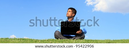 businessman with laptop sitting down on grass and looking up