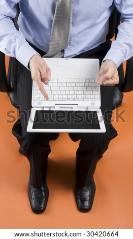 Businessman with laptop sitting in leather office chair pointing at screen