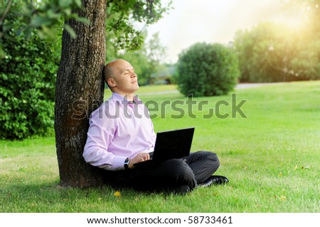Businessman with laptop sitting near a tree in the park
