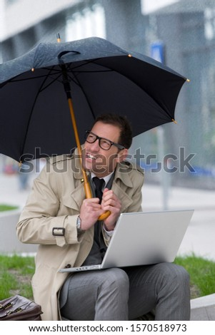 Businessman with laptop under umbrella in the rain