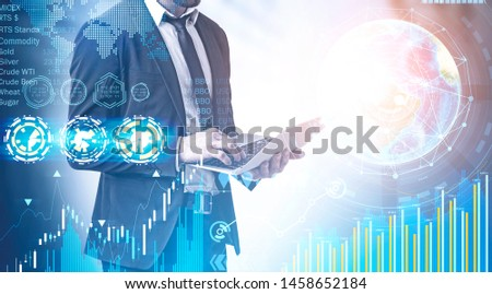Businessman with laptop working with business infographics interface. Concept of stock market and hi tech. Toned image double exposure. Elements of this image furnished by NASA #1458652184
