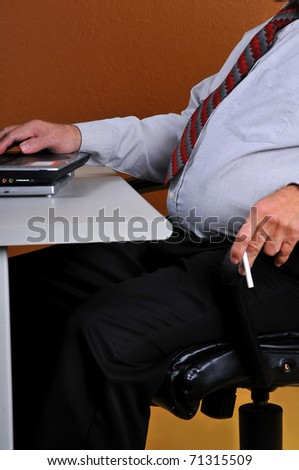 Businessman with large stomach, holding a cigarette working at his desk. Man displays poor eating habits, posture and vices. Can lead to physical problems.