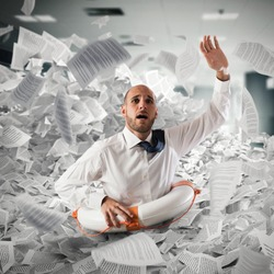 Businessman with lifebuoy sinks between worksheets in office