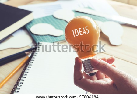 Businessman with lightbulb on desk in workplace. Ideas, creativity, inspiration and start up concept