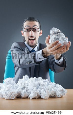 Businessman with lot of discarded paper